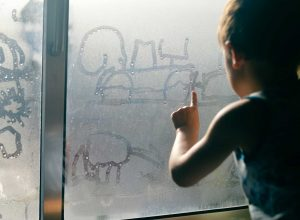Boy Drawing in Window Condensation